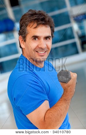 Man at the gym lifting a free-weight and smiling