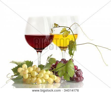 Gläser Wein und reifen Trauben mit Blätter, isoliert auf weiss