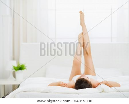 Woman In Bed Enjoying Her Beautiful Legs. Rear View