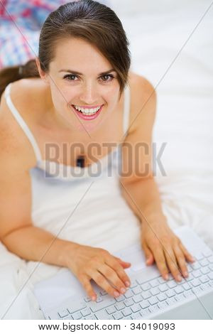 Smiling Woman Laying On Bed And Working On Laptop. Upper View