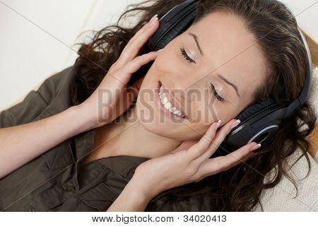 Closeup portrait of happy woman enjoying music with eyes closed via headphones.