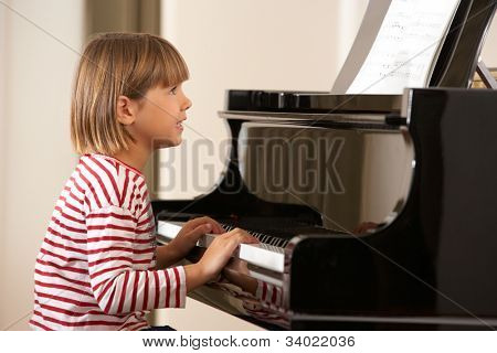 Young girl playing grand piano at home