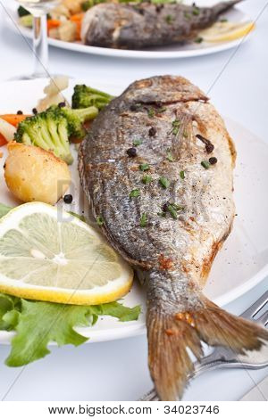 two servings of Sea Bream fish with vegetables on white plate