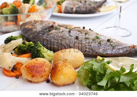 two servings of Sea Bream fish with vegetables and a glass of wine