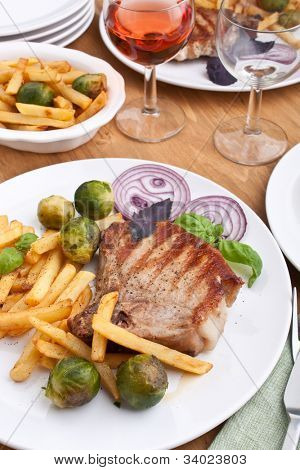 two servings of pork chops with fries and brussels sprouts and red wine