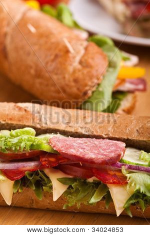 long sub sandwiches with salami on wooden table