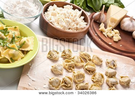 raw stuffed pasta on a cutting board and herbs, cheese and garlic