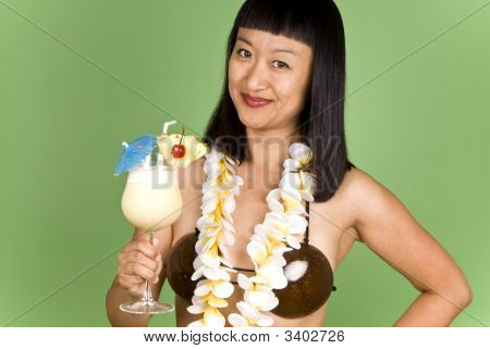 Asian Woman In Hula Girl Outfit Holding A Glass Of Pina Colada