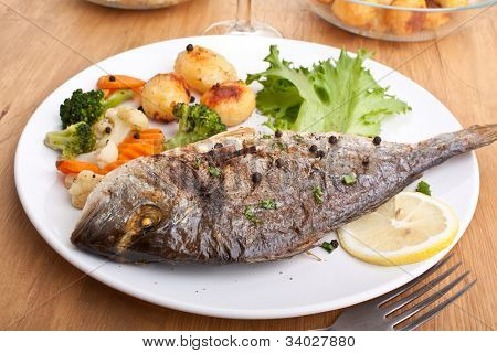 Sea Bream fish with vegetables on white plate close-up