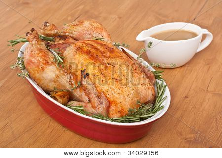 whole roasted stuffed turkey  in a dish with gravy