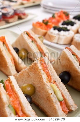 club sandwich with salmon and cucumbers on white bread