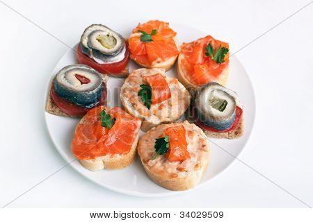 Grupo de sanguchitos (canapé) con arenque y salmón ahumado en un plato blanco