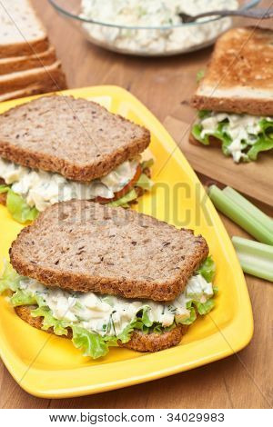 egg salad sandwiches on brown toasted bread and ingredients