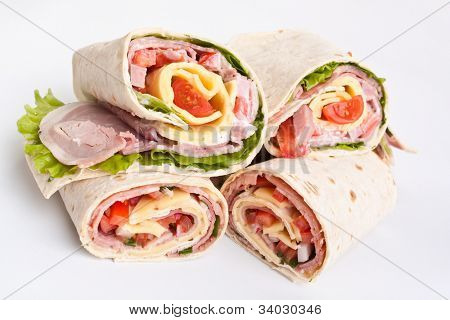 stack of wrapped tortilla sandwich rolls cut in half on white background