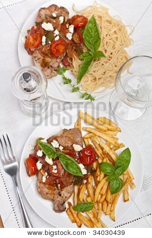 two servings of pork chop with tomato, onion and garlic  sauce garnished with french fries, pasta and  feta cheese