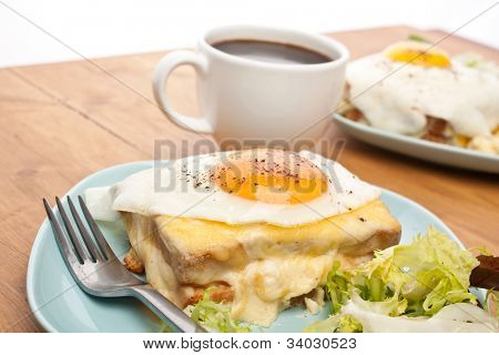 Two Servings of Croque Madame (Ham, Cheese, Bechamel Sauce and Egg Toasted Sandwich) garnished with fresh green lettuce salad and a cup of coffee