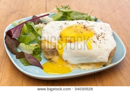 Serving of Croque Madame (Ham, Cheese, Bechamel Sauce and Egg Traditional French Toasted Sandwich) garnished with fresh green lettuce salad on a wooden table