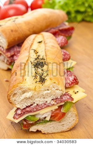 two halves of long baguette sandwich with lettuce, vegetables, salami and cheese on a wooden table and ingredients