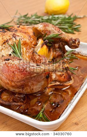 whole roasted stuffed chicken in a dish on a wooden table