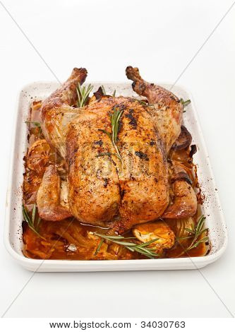 whole roasted stuffed chicken in a dish on white background