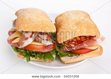 Ciabatta bread sandwiches stuffed with meat, cheese and vegetables on white background