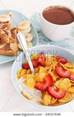 bowl of cornflakes and strawberries with yogurt, plate of chocolate and peanut buttered toasts and a cup of hot cacao on a table