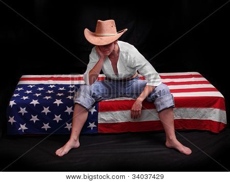 Depressed cowboy on a american flag. Economic crisis metaphor.