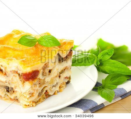 Delicious Italian Lasagna / with fresh basil / white background and copy space