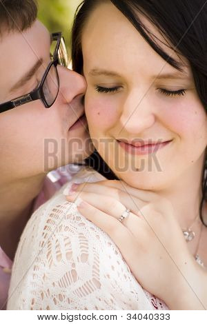 Young Engaged Couple Sharing a Tender Moment in the Park.
