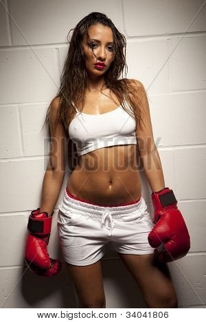 Beautiful exhausted female boxer damp with perspiration posing againt a white tiled wall