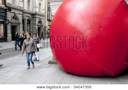 A passerby looks at Kurt Perschke's giant Red Ball that was squeezed into the entrance of the Guildh