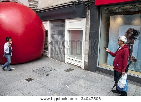Passersby is photographed on a mobile phone while possing by Kurt Perschke's giant Red Ball that was
