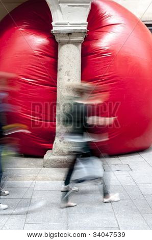 Passersby look at Kurt Perschke's giant Red Ball that was squeezed into the entrance of the Guildhal