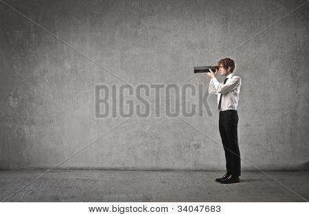 Junger Geschäftsmann mit einem Teleskop