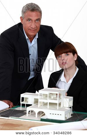 Architects posing with a building model