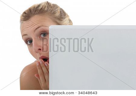 Surprised woman peering out from behind her laptop