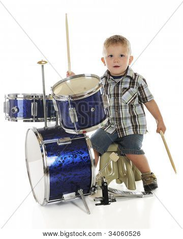 A young preschooler looking at the viewer as he plays on a drum set.  On a white background.