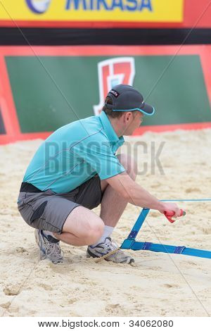 MOSCOW, RUSSIA - JUNE 8: Referee check the court after a technical timeout during Beach Volleyball Swatch World Tour in Moscow, Russia at June 8, 2012