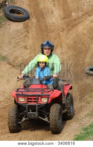 Dad With Son Riding A Quad Bike