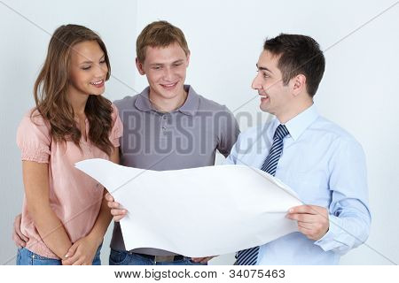 Male architect presenting the plan of the future home for the family of two