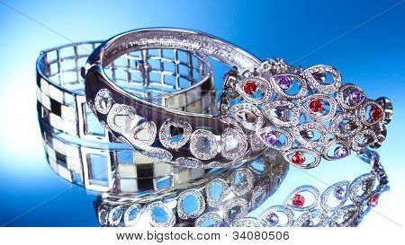 Beautiful silver bracelets on blue background