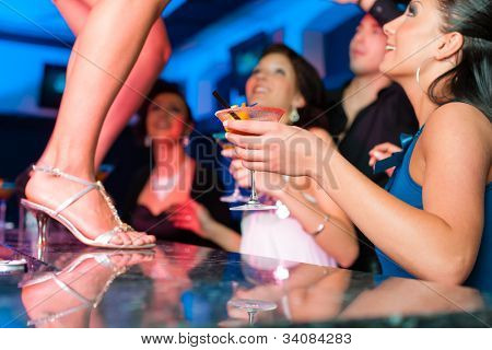 People having a party in club or bar, one woman is dancing on the table