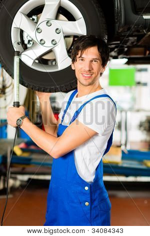 Young man in blue overall - mechanic - working with lamp on jacked car in a service station
