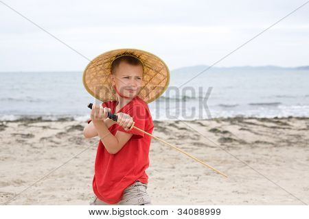 Boy plays with a samurai sword made of bamboo.