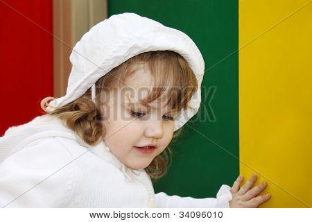 schönes kleine Mädchen tragen weiße Panama spielt bei Spielplatz