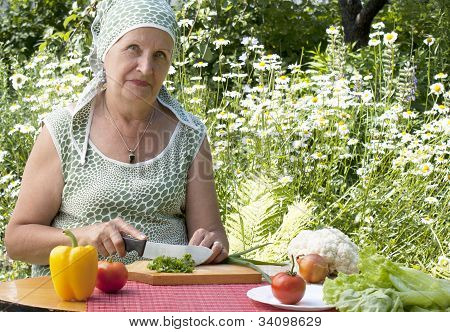The happy woman cuts salad