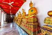 Statues Of Buddha In Wat Pho Temple, Bangkok Thailand. Golden Statues Are Placed In Row In Ancient S poster