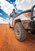 South Australia – Outback desert with 4WD on track under cloudy sky poster