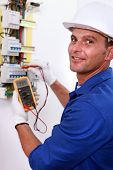 stock photo of electricity meter  - Smiling electrician using multimeter on electric meter - JPG