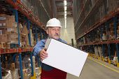 Worker In Uniform And Hardhat Carrying Box In Warehouse